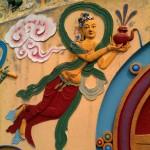 Eine verspielte, bunte Malerei auf einem Brunnensockel. Schräg wie fliegend trägt eine Frau mit rotem und grünem Gewand eine Teekanne vor sich her und gießt in den Brunnen.