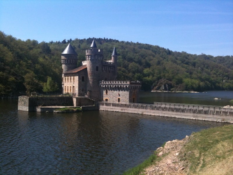 Ein Wasserschloss auf einer kleinen Insel in einem Fluss. Die Landschaft ist hügelig und bewaldet.