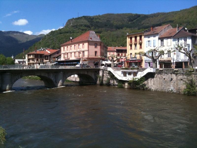 Ein breiter Gebirgsfluss fließt durch eine Stadt mit gut schützenden Hochwassermauern. Eine Brücke verbindet die beiden Stadtteile