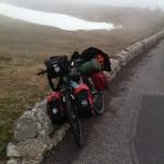 Ein Fahrrad mit viel gepäck lehnt an einer steinernen Brüstung vor nebliger, mit Schneeplacken durchsetzter Berglandschaft.