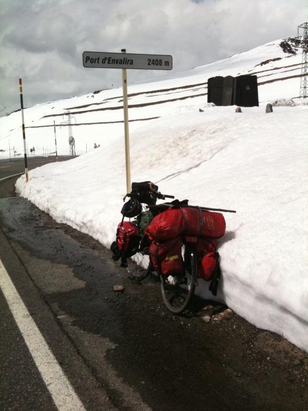 Reiserand auf freigeräumter, grauer Teerstraße neben verschneiter Gebirgsgegend