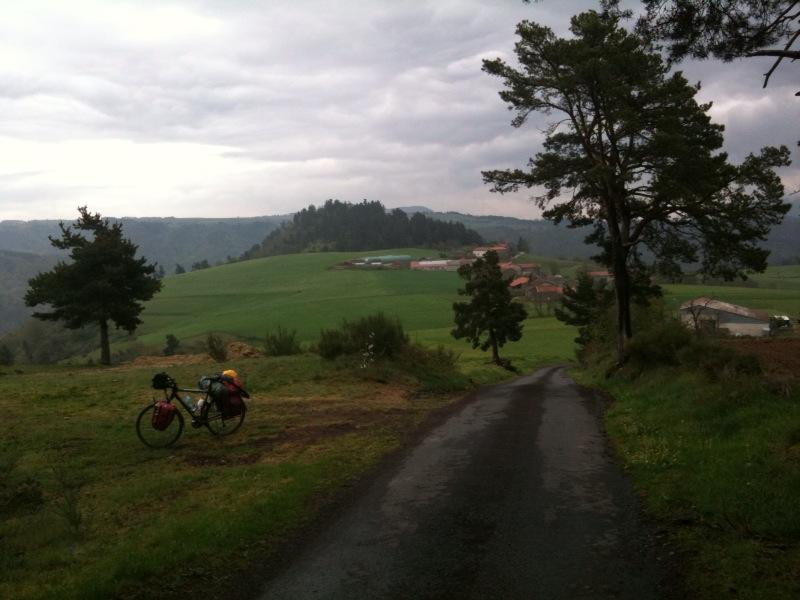Eine einsame, schmale Straße in grüner, wolkenverhangener Landschaft. Links im Bild ein Reiserad.
