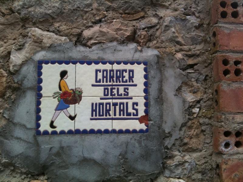 Auf Keramik steht der Straßenname Carrer dels Hotals neben einer abgebildeten folkoloristischen Figur
