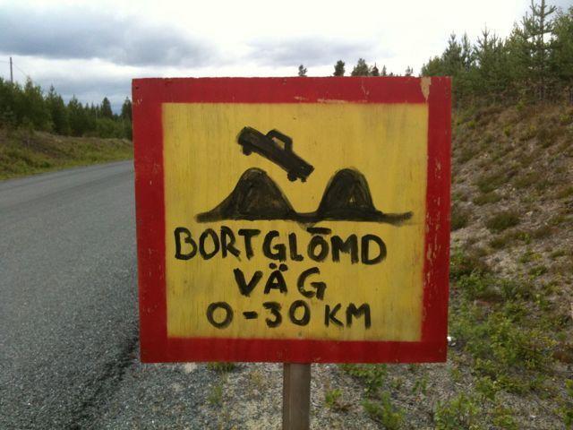 Handgemaltes Schild, das auf eine unwegsame Straße hinweist. Ein Auto holpert über zwei kamelhöckerähnliche Hügel. Gelb, rot, schwarz, schwedische Schrift: Bortglomd Väg