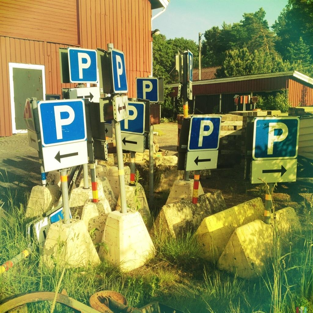 Viele Parkplatzhinweisschilder auf Betonständern