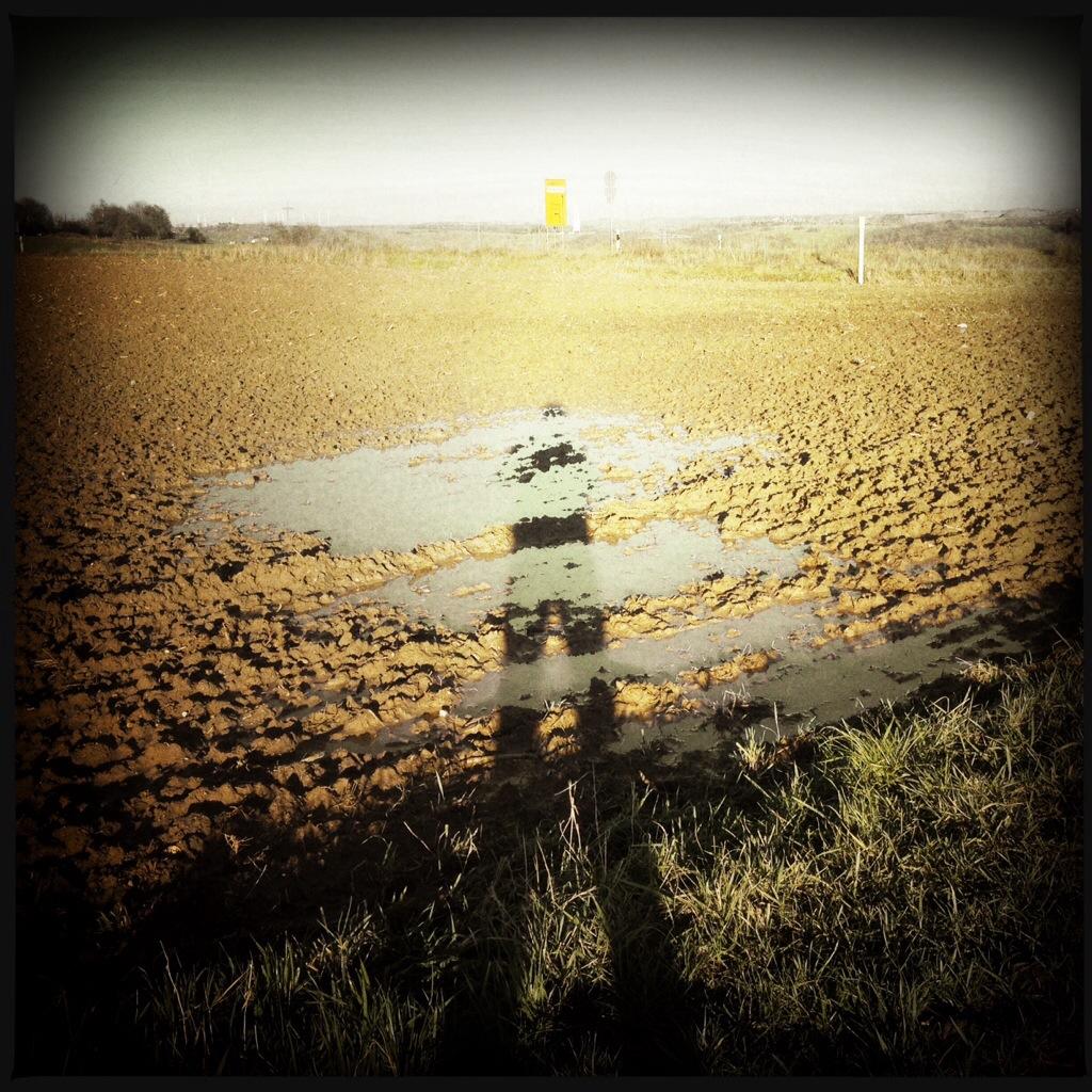 Schatten des Reisekünstlers Irgendlink auf Acker mit Pfütze