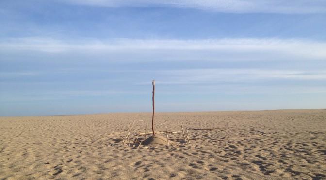 Pfosten auf Sandstrand vor Meer.