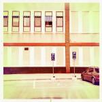 Ein Zweckgebäude aus Stahl und Beton mit vielen Fenstern, gelblich verfärbt im Retrostil. Daneben ein parkendes Auto.