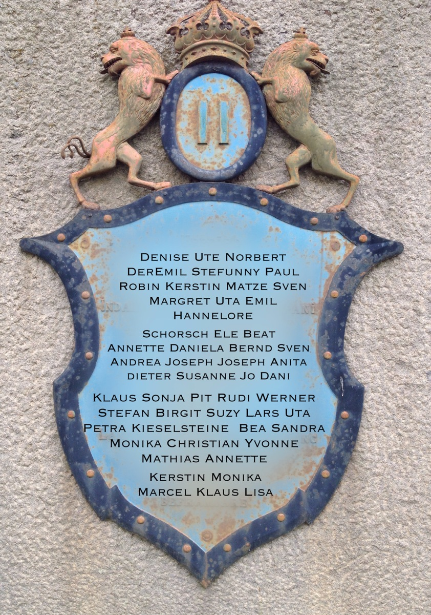 Hellblaues Wappen auf Granit, mit verzierter Umrandung, zwei Löwen darüber, die eine Krone stützen  - die Namen der Unterstützer stehen auf der Tafel.