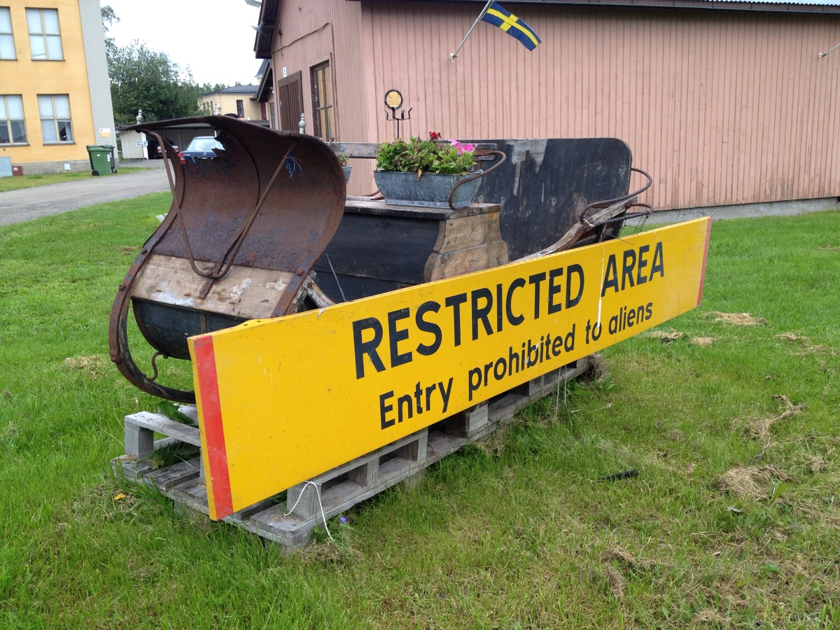 Rentierschlitten vor ehemaligem Kasernengebäude und ein Schild mit der Aufschrift Restricted Area
