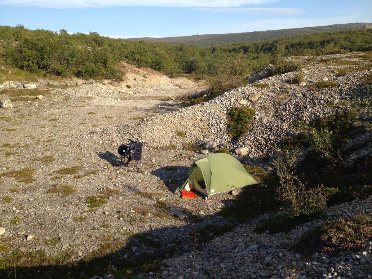 Zelt und Fahrrad in einer windgeschützten Kiesmulde an der Barentssee