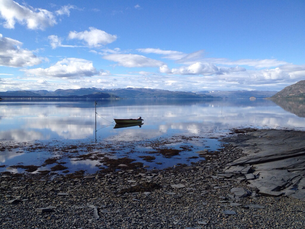 Unterwegs nach Alta. Strandidyll auf Norwegisch: dunkelgrauer, steiniger Strand, blaue See, blauer wolkiger Himmel & Boot