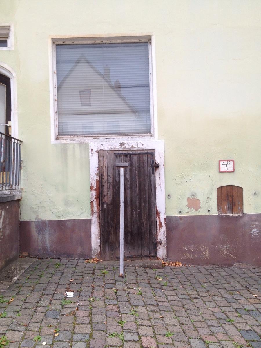 Verbarrikadierte  Kellertür mit Fenster, in dem sich das Haus gegenüber spiegelt