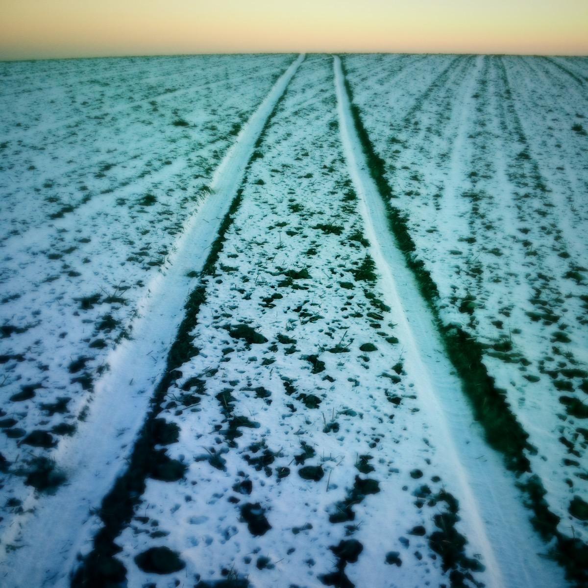 Schnurgerade Traktorspur im Schnee auf Acker, grünlich-blau verfremdet mit einem winzigen Streifen dreckig gelben Himmels.