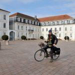 Reiseradler vor barockem Rathaus mit Walmdach.