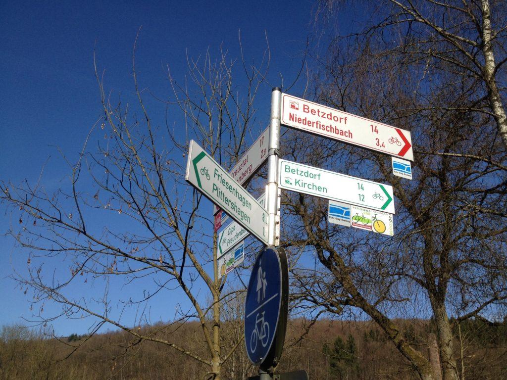 Nahe Kirchen erkennt man die Landesgrenze Nordrhein-Westfalen/Rheinland-Pfalz an unterschiedlich farbigen Radweghinweisschildern.