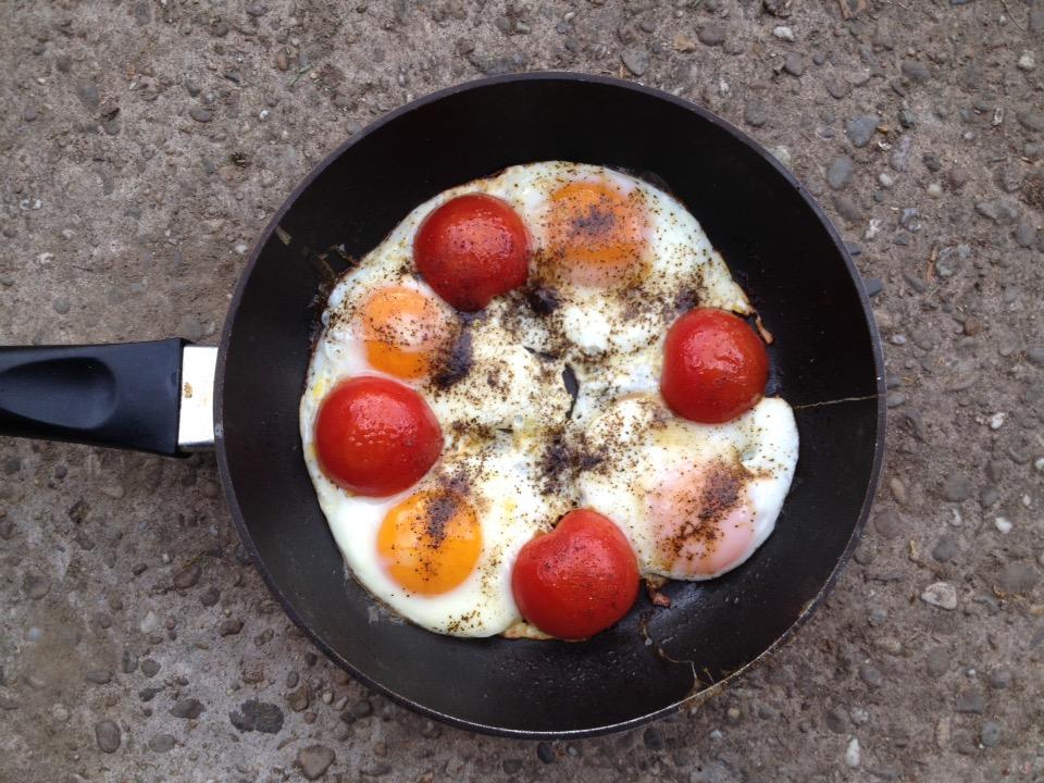Vier Spiegeleier und vier halbe Tomaten in Pfanne kreisförmig symmetrisch angeordnet.
