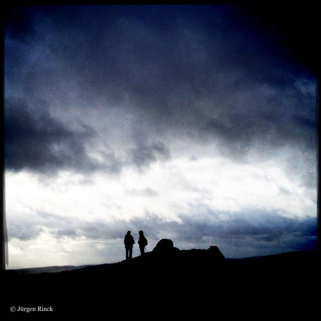 Silhouette zweier Wandererinnen vor Wolkenbehangenem Himmel
