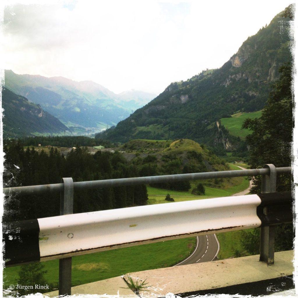 Hinter einer Leitplanke öffnet sich das Tal und der Blick auf eine Halde. Man erkennt Spuren und eine sich schlängelnde Straße.
