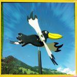 Ein Windrad aus Rabenfigur mit gelbem Schnabel vor blauem Himmel.