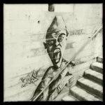 In einem Treppenhaus hinterm Stahlgeländer sieht man ein Monster mit spitzem Glatzkopf und weit aufgerissenem Mund.