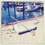 Ein Kehrbesen auf einer Hafenmauer. Dahinter kleine Fischerboote.