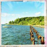 Stählerne Pfosten verrostet im Meer. Ein Segelboot vor Anker. Grün bewachsenes Ufer.