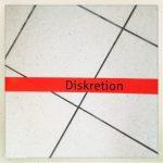 Das Wort Diskretion auf einem roten Streifen, der schräg über weiße Bodenfließen verläuft.