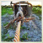 An rostigem Drahtseil hängt ein Stahlkorb, mit dem Sand gefischt wird.
