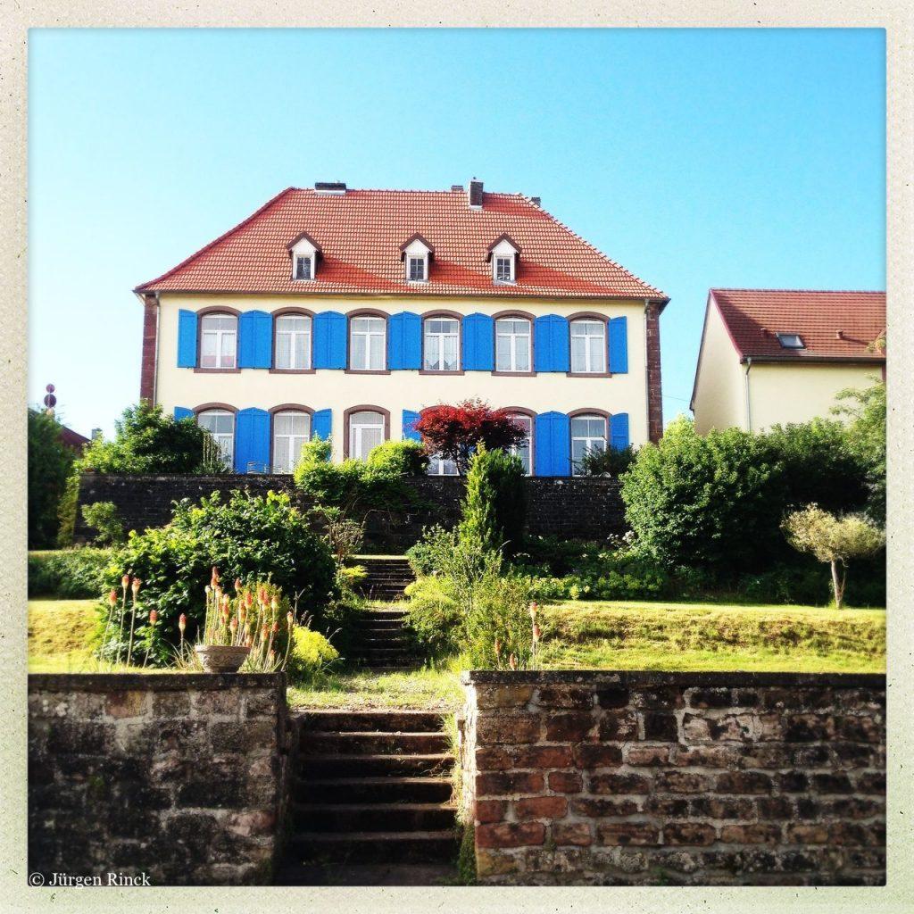 Ein barockes Haus mit Walmdach in Volmunster, Lothringen.
