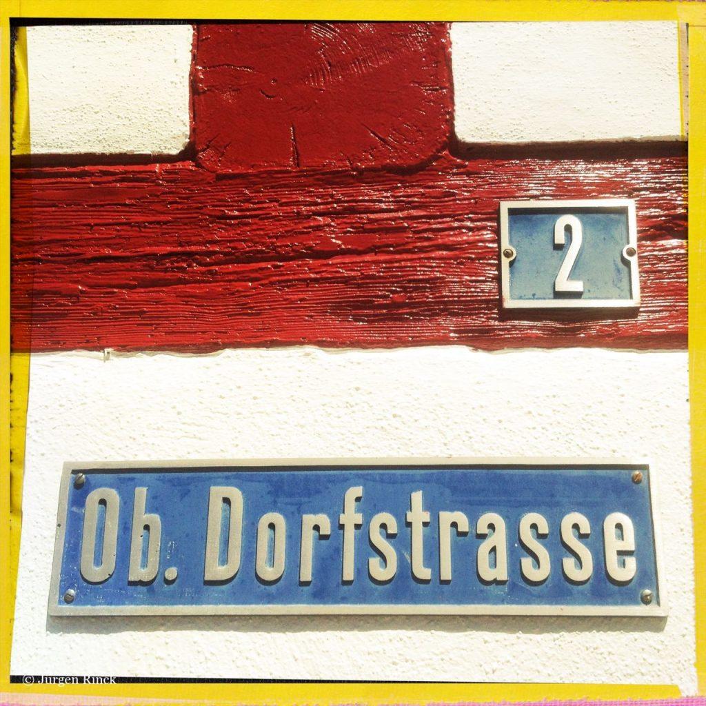 Haus Nummer zwei an rotem Fachwerkbalken. Darunter ein Schild Ob. Dorfstraße.