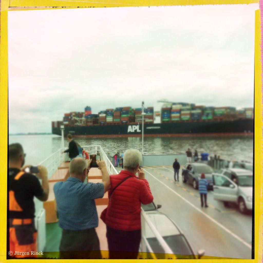 Drei Männer mit dem Rücken zum Betrachter fotografieren ein Containerschiff von der Aussichtsplattform eines Elbfährschiffs.