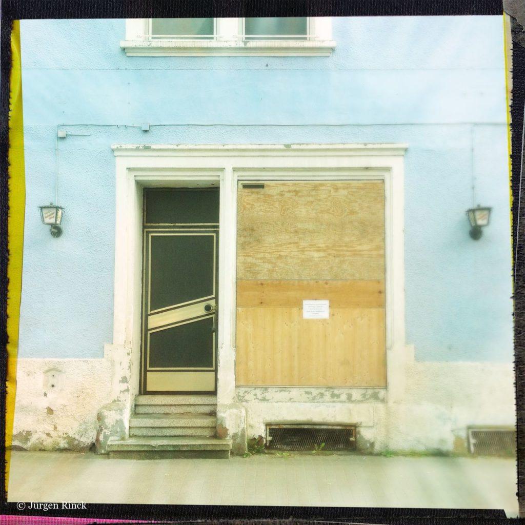 Eingang eines ehemaligen Dorfladens. Das ehemalige Schaufenster ist verbrettert.