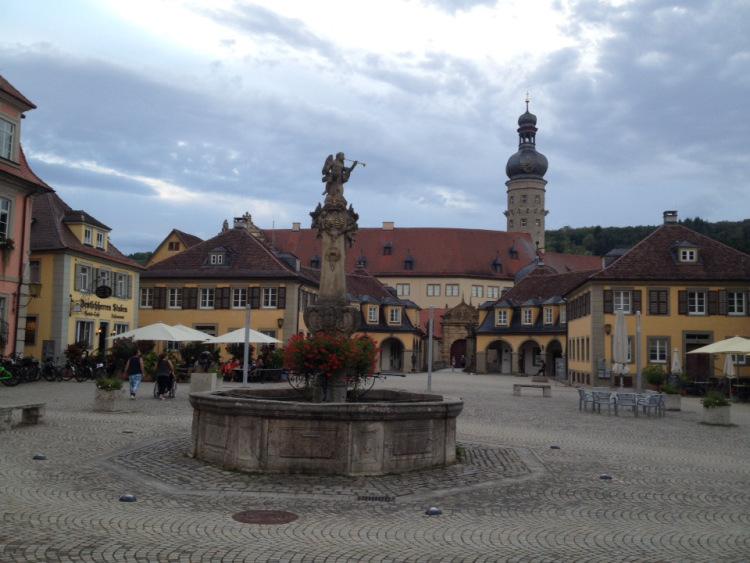 Dorfplatz mit achteckigem Dorfbrunnen samt Mittelsäule. Im Hintergrund Häuser, darüber wolkiger Frühabendhimmel.