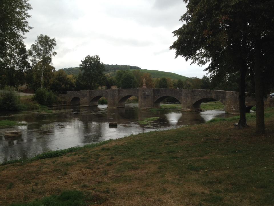 Eine fünfbogige flache Steinbrücke, grüngrau über einen Fluss, der kaum Wasser führt.