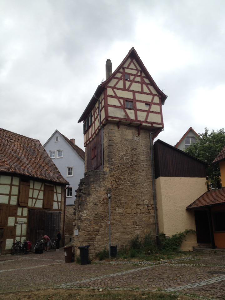 Ein Fachwerkhaus mit roten Balken und spitzem Dach auf einem Sockel aus behauenen grün-grauen Steinen.