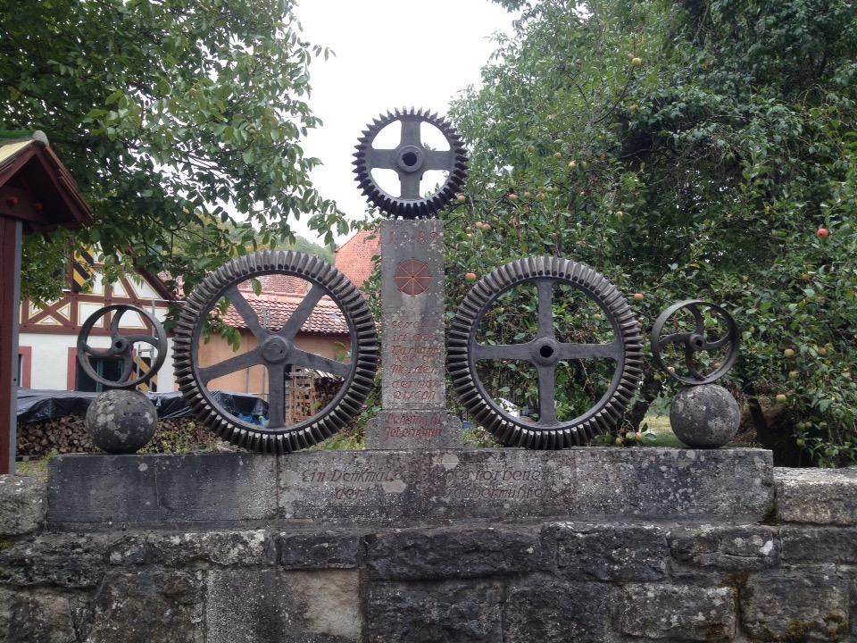 Drei alte Getriebe-Zahnräder etwa halbmeter groß wie sie in Mühlen verwendet wurden stehen auf der Brüstung einer Brücke. In Stein gemeiselt erinnert man an die vielen Mühlen des Taubertals, die nicht mehr sind.