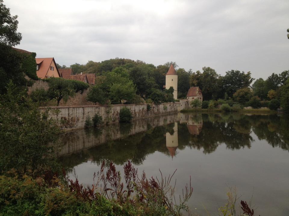 Eine mittelalterliche Stadtmauer mit Wehrturm spiegelt sich in einem Weiher.