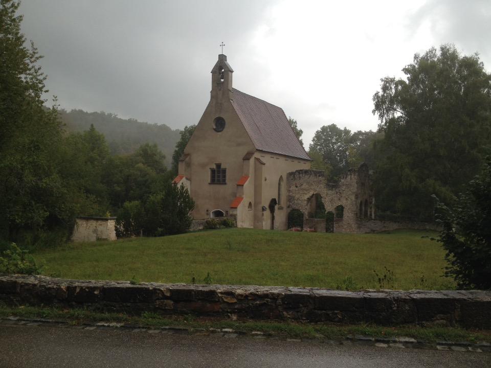 Unter verregnetem Himmel steht eine Kirche, deren rechter Flügel eine Ruine ist.