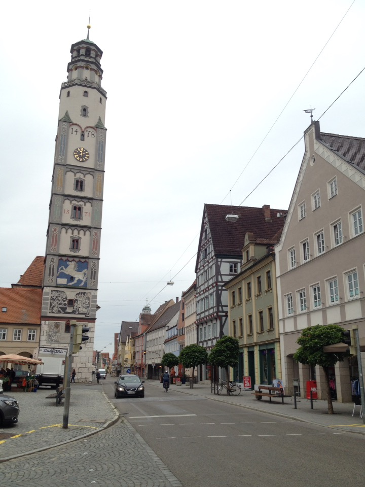 Ein quadratischer Turm mit rundem Dach neben einer Durchfahrtstraße, die von Häusern gesäumt ist.
