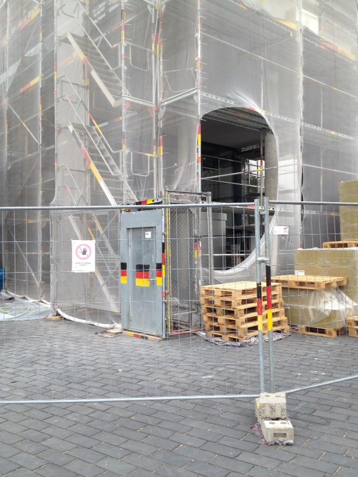 Abgesperrte Baustelle. Die Bauzäune und die Tür sind in Deutschlandfarben markiert.