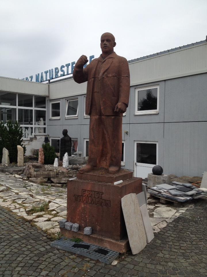 Braune, lebensgroße Statue auf Sockel mit Inschrift Ernst Thälmann. Im Hintergrund ein Verwaltungsflachbau.