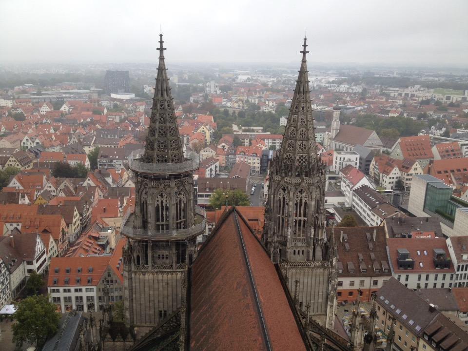 Blick von oben auf das Satteldach einer Kirche und zwei Lirchtürme. Im Hintergrund das Häusermeer der Stadt.