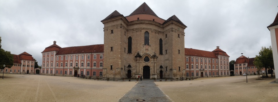 Panoramabild eines strengen Klostrrgebäudes mit zentralem dreifach Turm.
