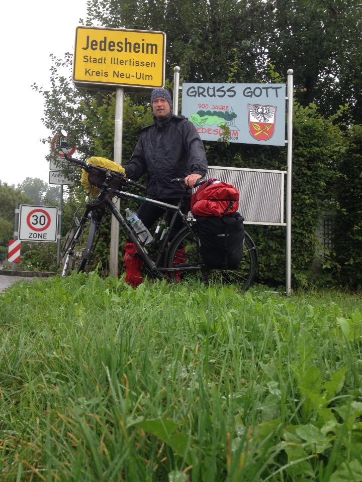 Radler posiert mit Fahrrad vor dem Ortsschild von Jedesheim.