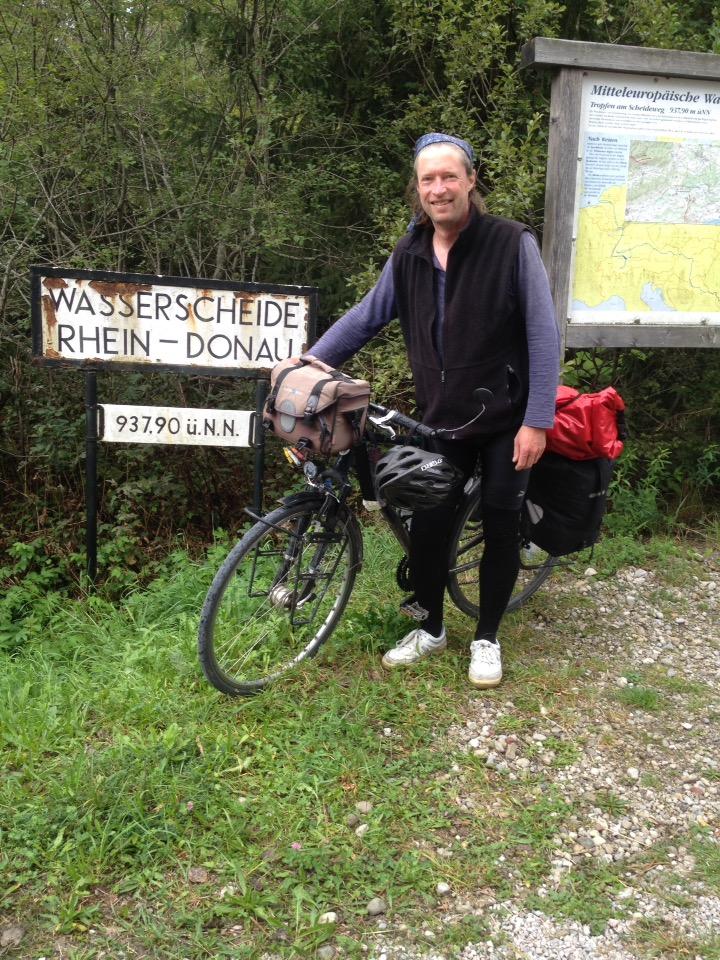 Radler mit Reiserad vor altem Schild, auf dem steht Wasserscheide Rhein-Donau 937 komma nochwas Meter.