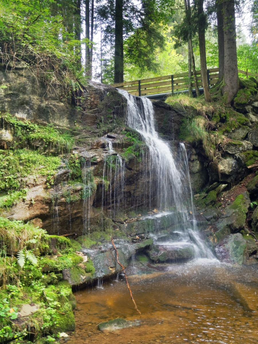 Ein etwa zehn Meter hoher Wasserfall unter einer Wandererbrücke mit wild bewachsenen Felsen. Im Bach liegen Steine.