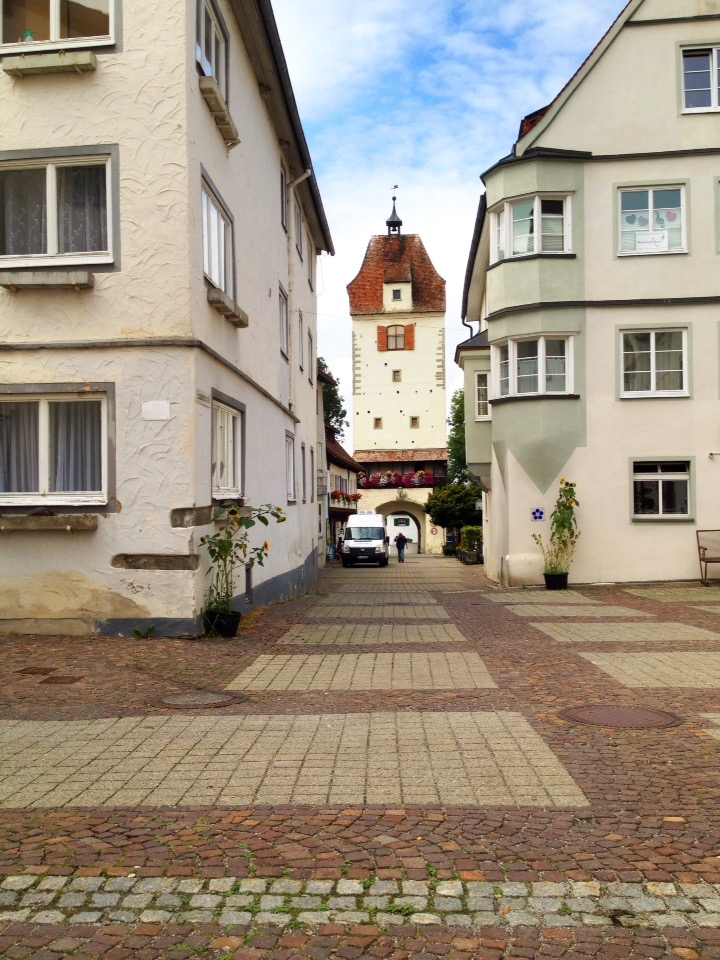 Blick eine gepflasterte Straße entlang auf einen weißen Tor-Turm.