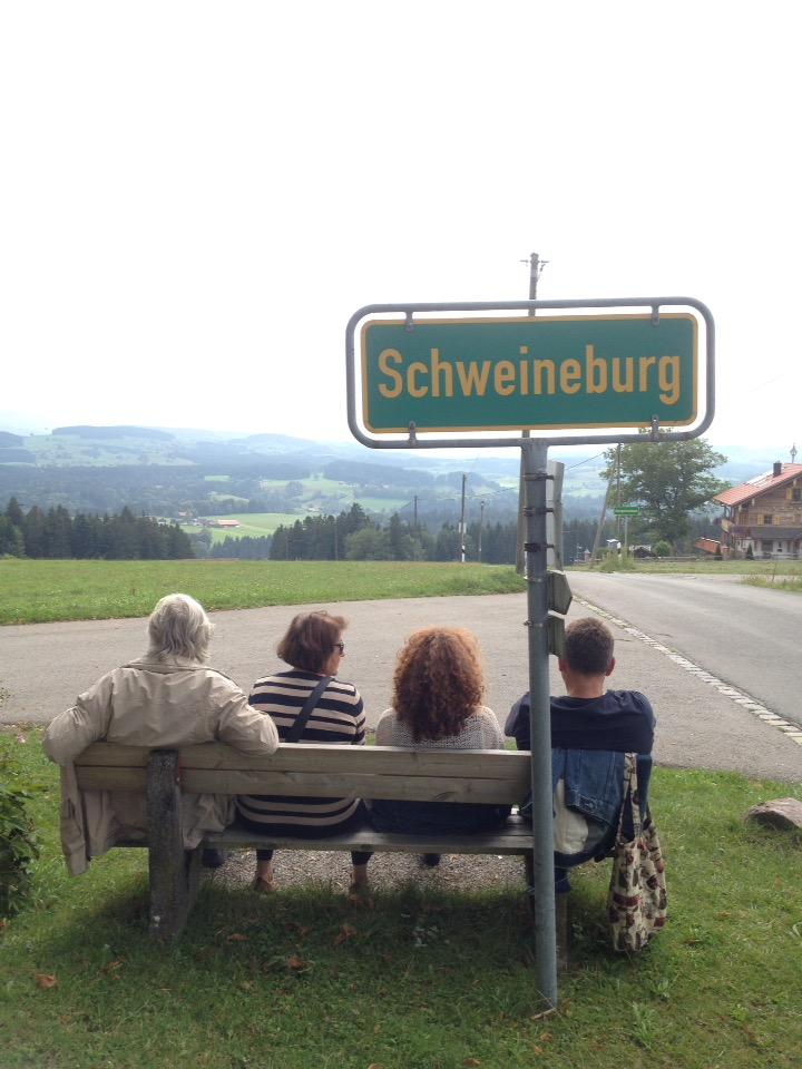 Vier Menschen, Rücken zum Betrachter auf Parkbank unter grünem Ortsschild Schweineburg schauen über weites Land.