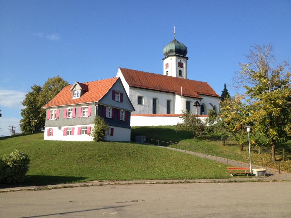 Eine Kirche mit Zwiebelturm. Links daneben ein Wohnhaus in hügeliger Voralpenlandschaft